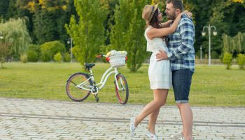 Couple kissing in front of a grassy area with a bike