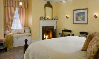 Bonner Room with bed, seating, and fireplace
