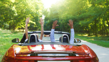Couple with their hands up while in a red convertible car