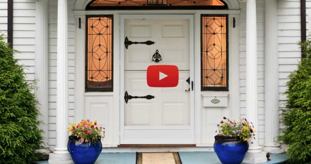 Front door with flower pots and bushes on the sides