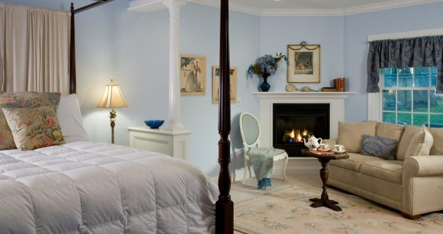 Room with bed, seating area, and fireplace
