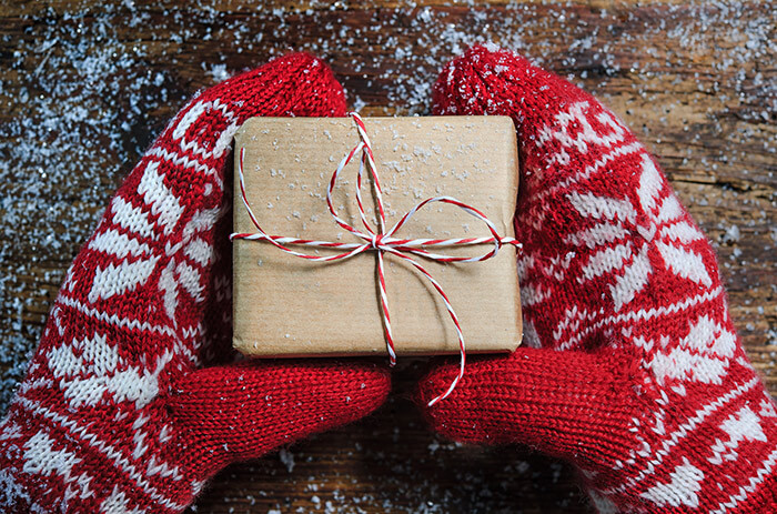 Hands with mittens holding a small gift box