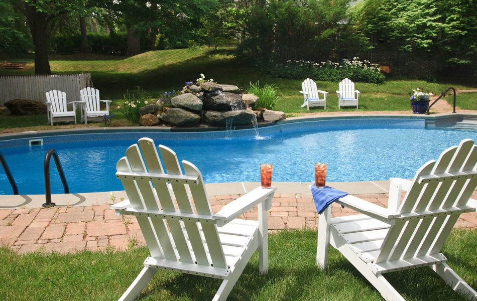 Iced tea on pool chairs by large blue pool