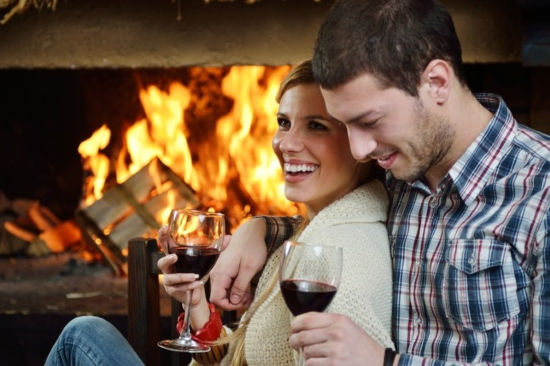 couple with wine cuddling by in-room fireplace