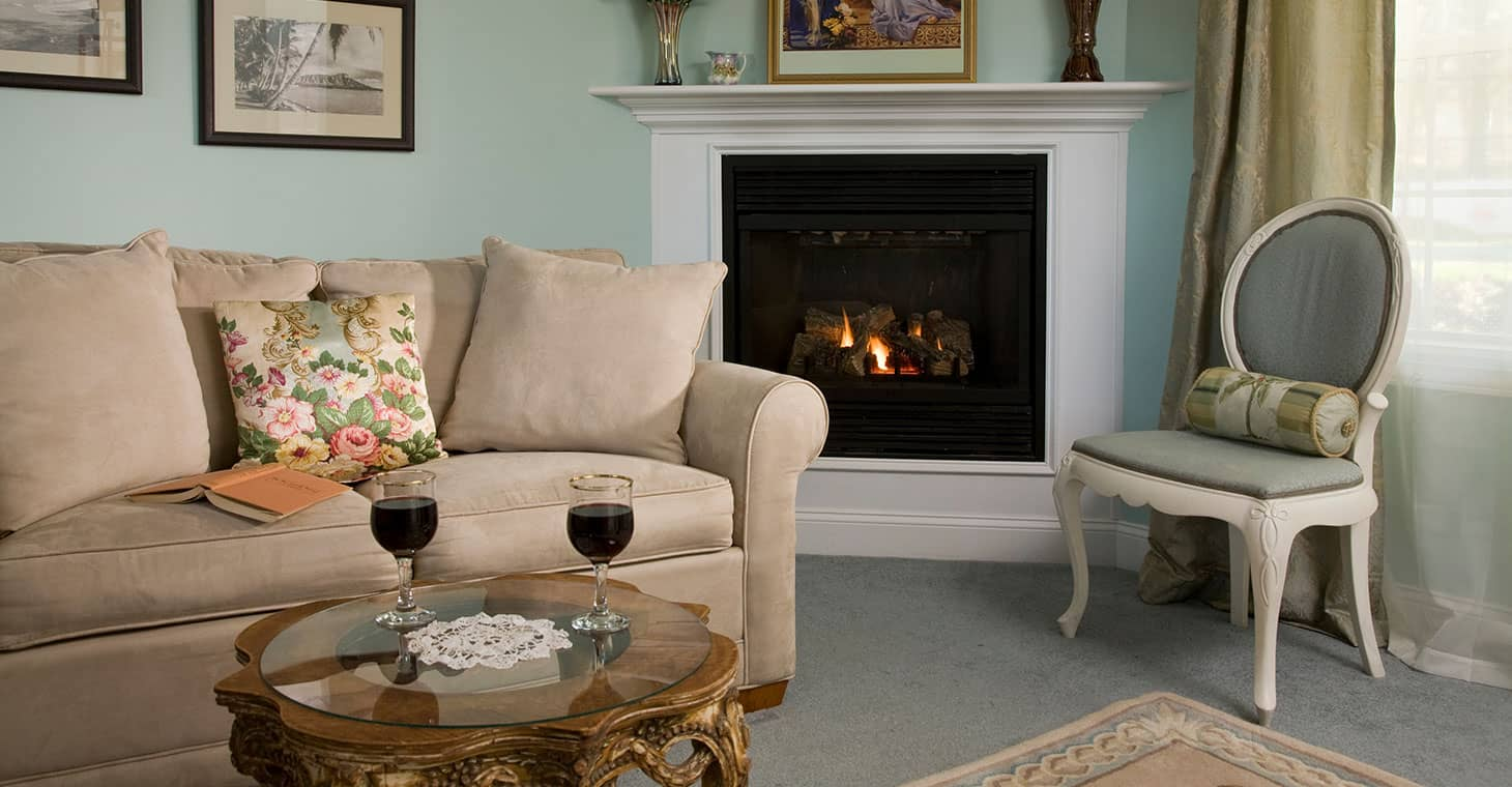Wine on a table by fireplace in cozy sitting area