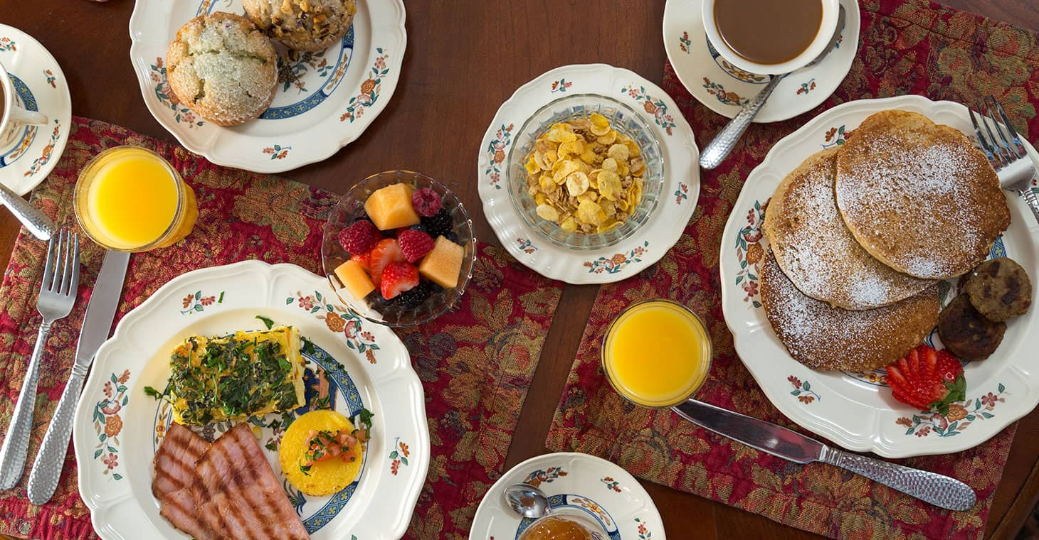 Assortment of delicious breakfast foods on plates at our Massachusetts boutique hotel