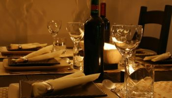 A dinner table set with plates and a bottle of wine