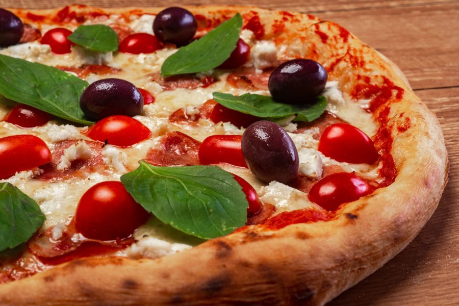 a pizza with basil and olives