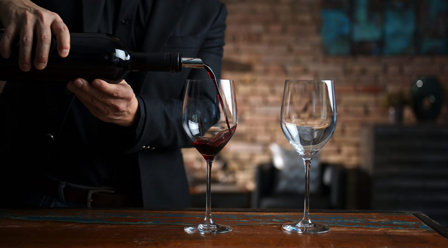 a server pouring two glasses of wine